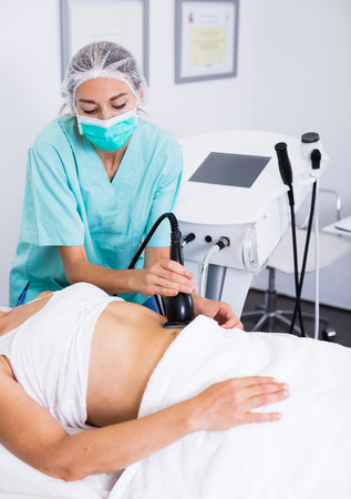 esthetics: Professional cosmetician performing cryolipolyse treatment in clinic of esthetic cosmetology Stock Photo