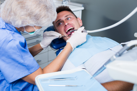 Male patient sitting on chair in dental office getting dentist treatment