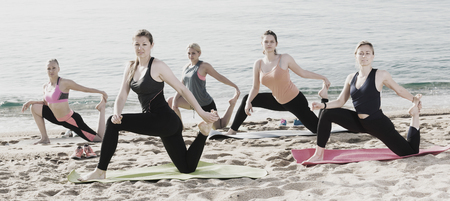 equilibrium: Group of smiling women practicing yoga positions on beach in sunny morning Stock Photo