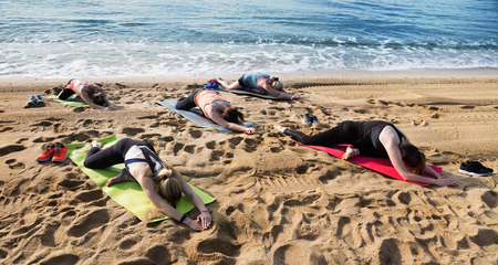 equilibrium: Group of young diligent  females performing yoga on sunny seaside