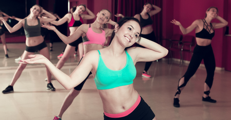 Young slim athletic females exercising dance training in class