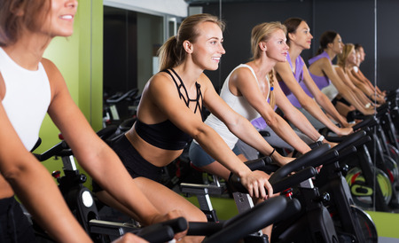 Young fit women cycling on stationary bike in gym