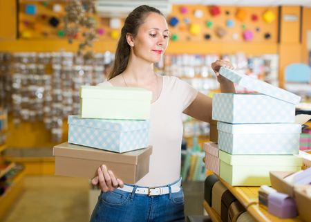 Woman 20-30 years old is choosing light boxes for gifts in store. Stock Photo