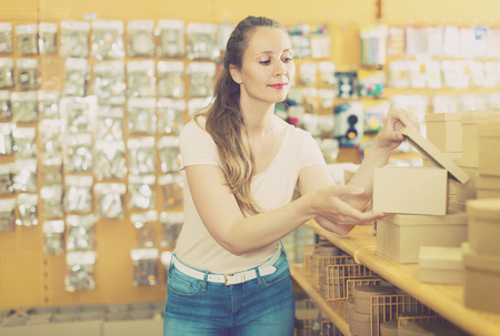 pasteboard: Woman is choosing small boxes for gifts in store.