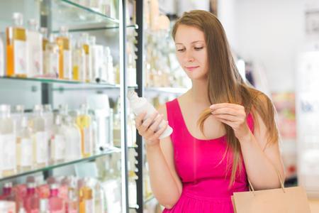 choise: Blonde young woman take a choise shampoo in perfume supermarke