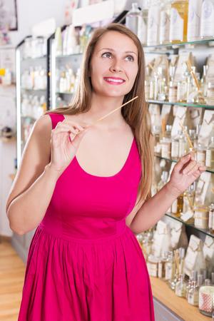 choise: HAppy young woman take a choise fresh perfume in perfume supermarket