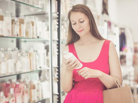 choise: Smiling woman take a choise shampoo in perfume supermarke Stock Photo