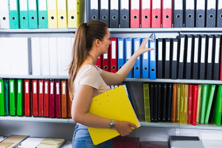 Woman is choosing folders on the shelves in stationery store.