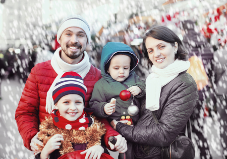 Ordinary smiling glad parents with kids choosing X-mas decorations in market Stock Photo