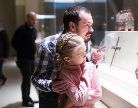 museum visit: Smiling father and daughter regarding religious art in museum
