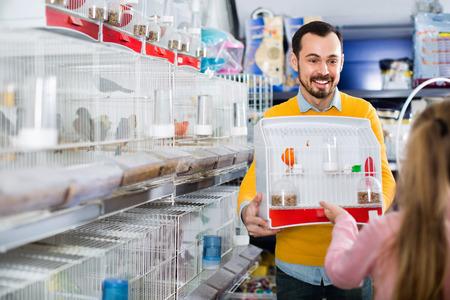 Jeune mâle heureux heureux vendeur montrant cage avec oiseau canari à la fille dans le magasin d & # 39 ; animaux Banque d'images - 87770167