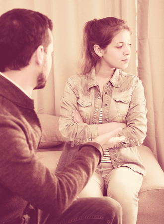 Young father quarrelling with his daughter teenager at home