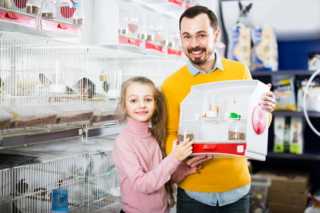Young man with a daughter showing cage with the purchase of a canary in a store