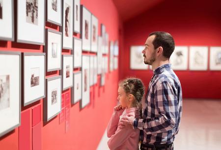 positieve vader en dochter kijken naar de tentoonstelling van foto's in het museum