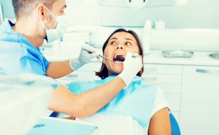 Diligent friendly  positive dentist is treating woman patient which is sitting in dental chair in clinic. Stock Photo