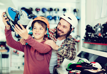 happy american  father and son deciding on new roller-skates in sports store