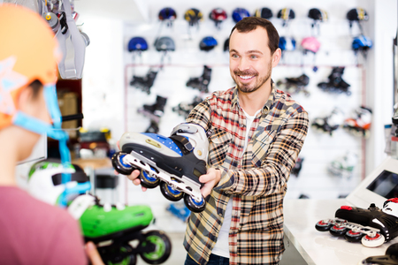Adult man seller assisting boy in choosing roller-skates in sports store