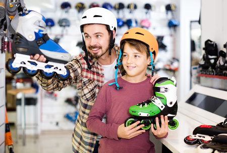 Young english father and son deciding on new roller-skates in sports store Imagens