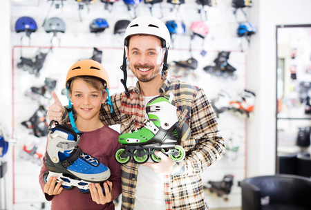 boasting: Ordinary father and son boasting purchased roller-skates in sports store