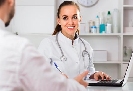 Visitante masculino médico diligente agradable mujer en el hospital