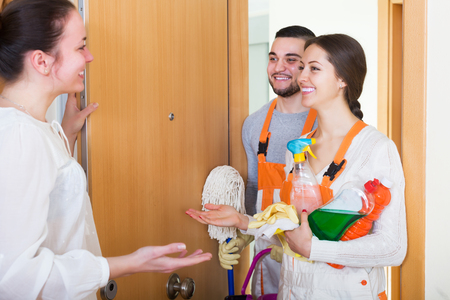 Professional positive cleaners with equipment standing at doors of client house Stock Photo