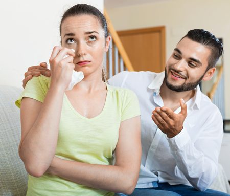 Young smiling  man talking to upset woman