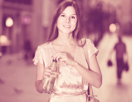 Young smiling american female drinking water in historic city center Stock Photo