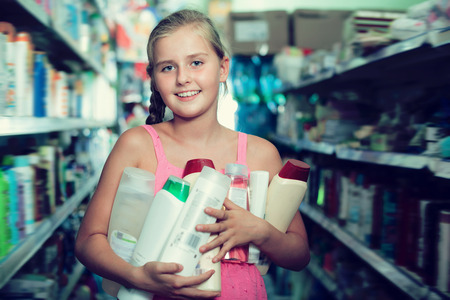 Smiling girl holding shampoo and shower gel at the supermarket