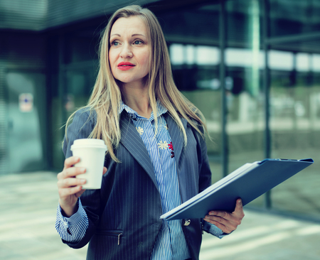 Professional woman in jacket walking with coffee and document folder