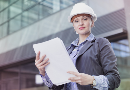 Smiling female architect in helmet with paper documents in the hand Stock Photo