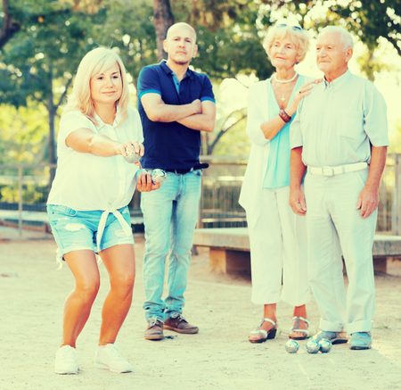 Happy positive smiling family playing petanque in outdoor
