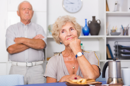 Elderly upset woman sitting separately having problems in relationship with husband
