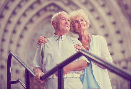 Portrait of romantic aged woman with husband posing near iron banisters outdoors