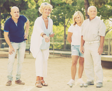 Group of mature people playing petanque in park at sunny day outdoor
