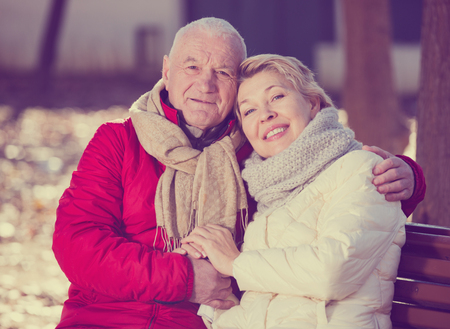 Mature man and woman sitting comfortably on bench in park