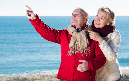 europeans: Aged husband and wife taking stroll on beach and watching skies Stock Photo
