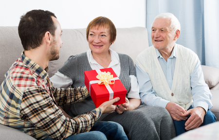 Son gives gift in red box for holiday to his parents at home
