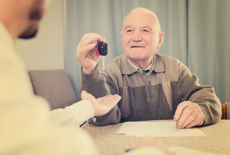 Aged man signing papers to sell his car at home Stock Photo
