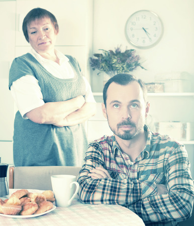 Mature mother teaches and instructs her son at table at home