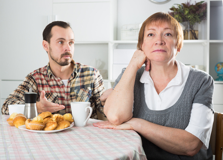 Elderly mother resents her son at table at home Stock Photo