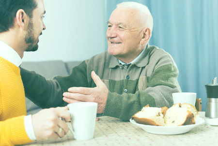 eldest: Smiling elderly father and son having breakfast and warmly talk at table at home Stock Photo