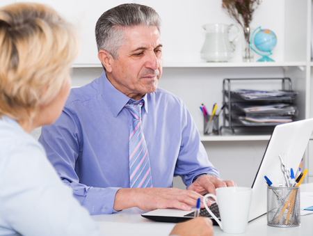 Mature head gives task to assistant at office at table