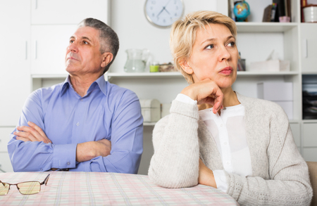 Mature man and woman are offended at each other because of the misunderstanding in his home.
