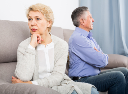 sad middle-aged couple quarreling at home with each other and take offense
