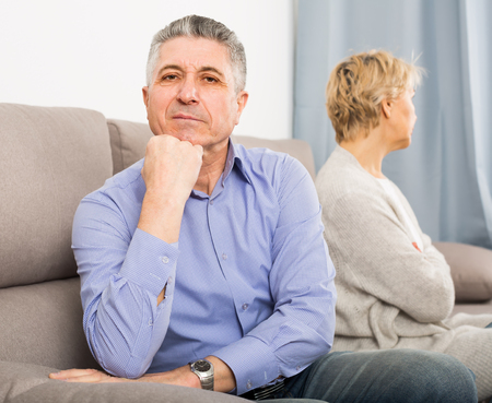 sad mature couple quarreling at home with each other and take offense