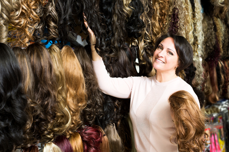 Pretty female shop assistant selling natural hail ponytails, tresses and wigs