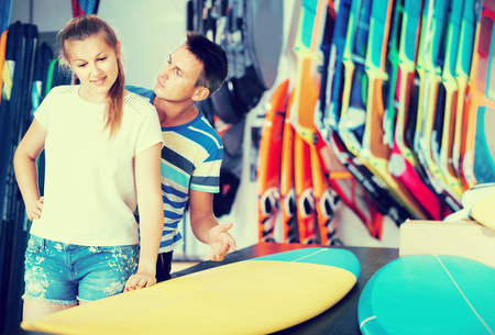 Smiling italian couple is choosing surfboard in nautical shop. Stock Photo