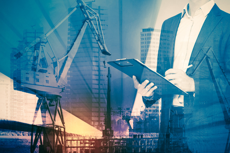 Double exposure of businessman and construction crane in rays of light