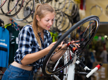 Portrait of nice female who is cheking wheels of bicycle in workshop indoors