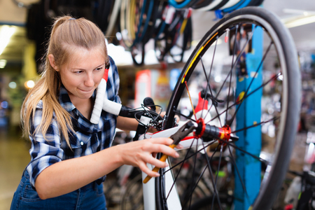 Portrait of happy cheerful   girl who is working with pliers and fixing wheels in workshop. Stock Photo